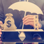 Financial risk assessment / portfolio risk management and protection concept : Businessman holds a white umbrella, protects a dollar bag on basic balance scale, defends money from being cheat or fraud