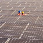two-men-hard-hats-standing-in-sea-of-solar-panels.jpg