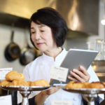 female-asian-bakery-owner-taking-inventory-with-tablet.jpg