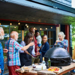 Multi racial step family preparing for barbecued lunch in garden, bonding, togetherness, food and drink
